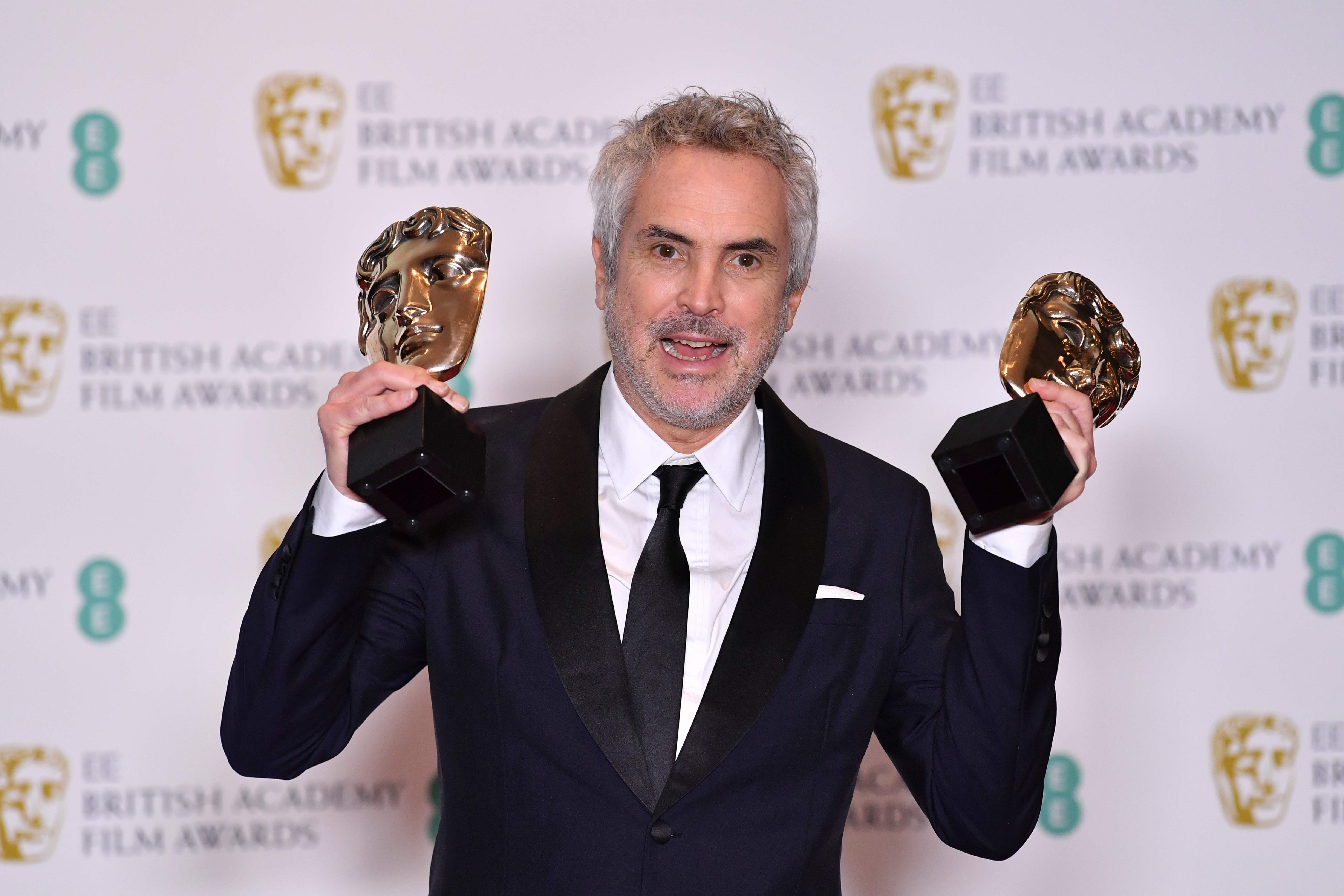 Mexican director Alfonso Cuaron poses with the awards for a Director and for Best Film for 'Roma' at the BAFTA British Academy Film Awards at the Royal Albert Hall in London on February 10, 2019 (Photo by Ben STANSALL / AFP)