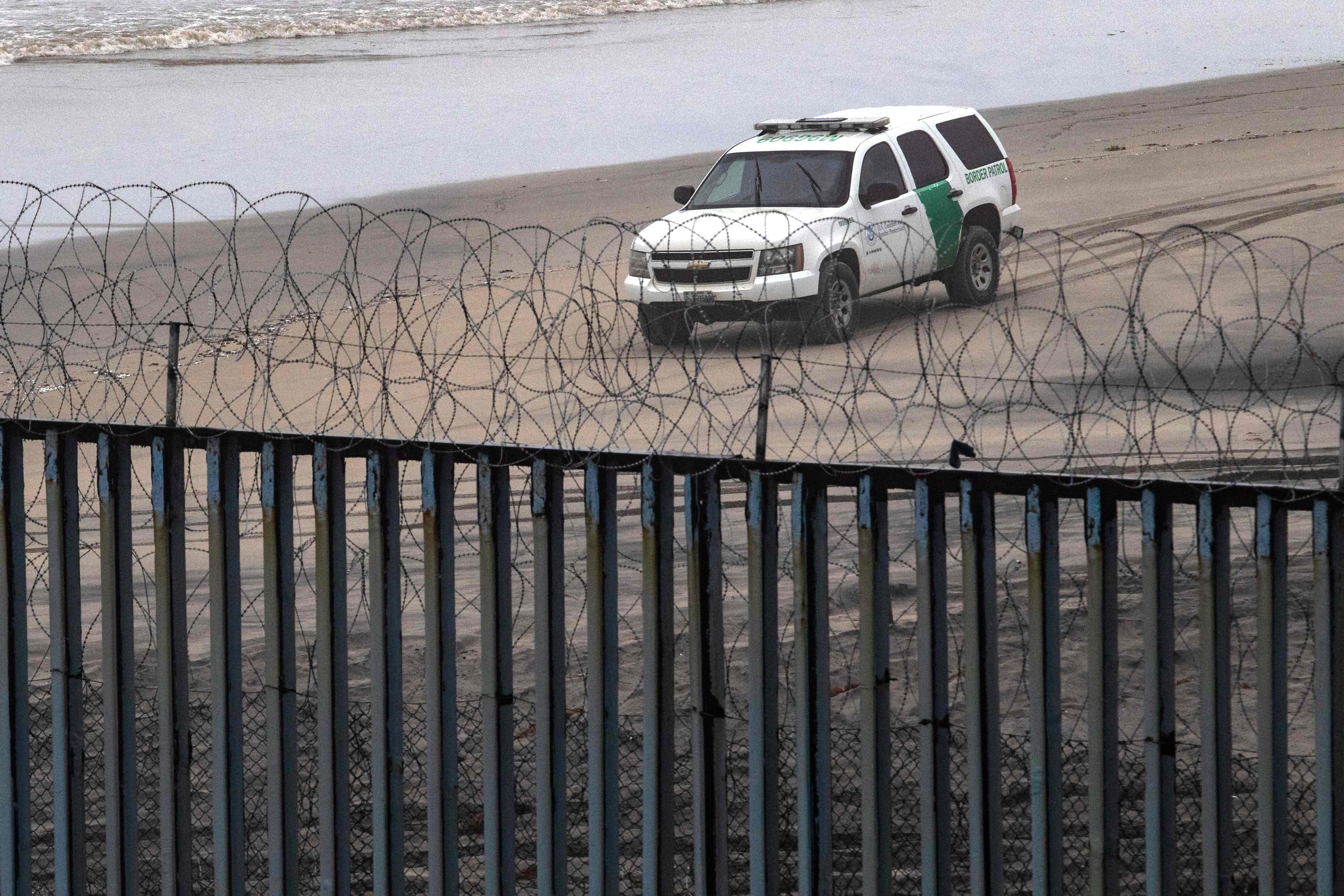 A Border Patrol unit remains near a section of reinforced US-Mexico border fence seen from Tijuana, Baja California state, Mexico, on February 14, 2019. - US President Donald Trump will sign a spending bill to avert a government shutdown but will also issue an emergency declaration to fund his controversial border wall, the White House and lawmakers said Thursday. (Photo by Guillermo Arias / AFP)