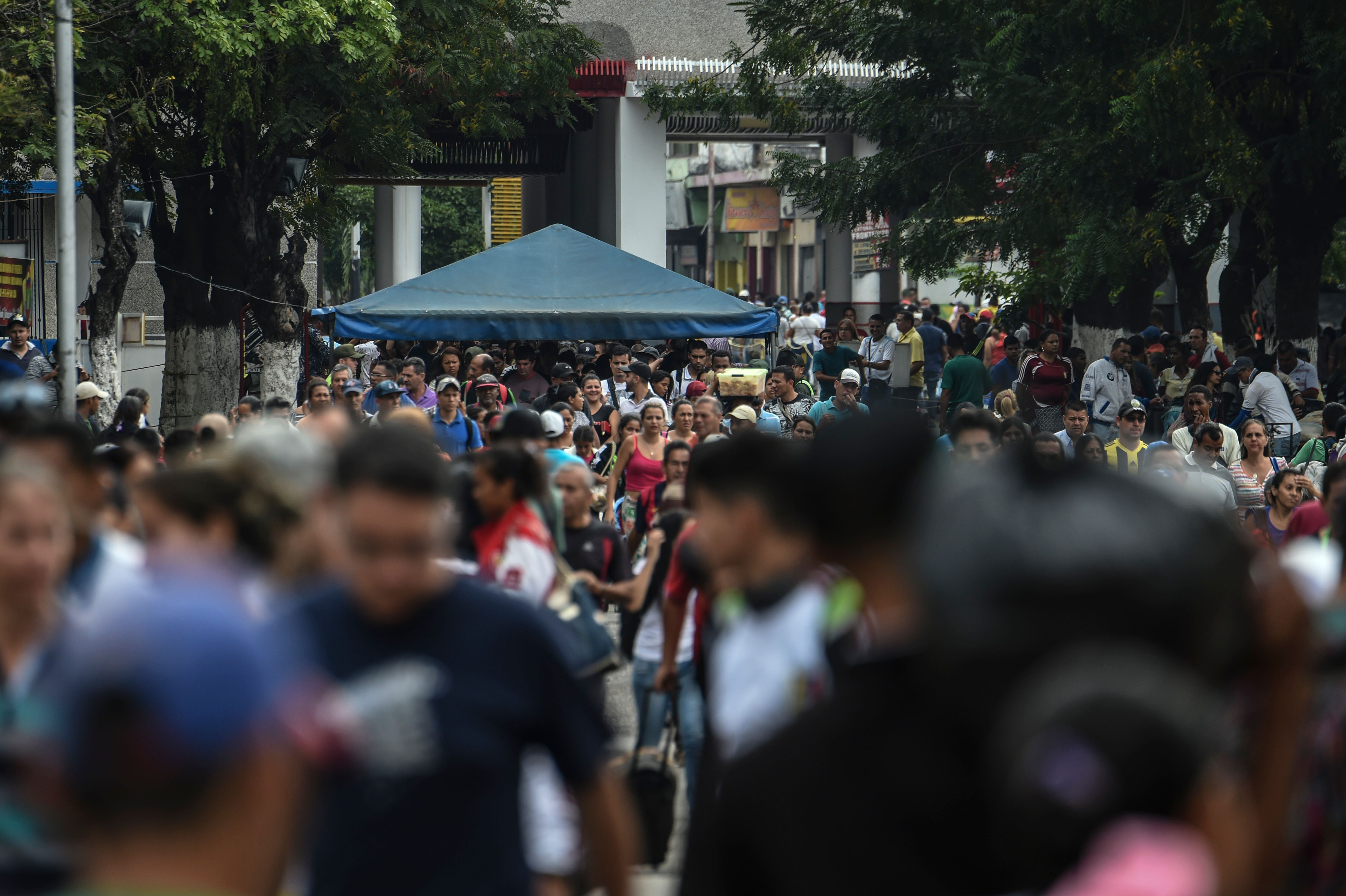 """Venezuelans cross the Simon Bolivar brige in San Antonio del Tachira, Tachira State, Venezuela, on the border with Colombia, on February 20, 2019. - Nicolas Maduro's government suspended """"indefinite flights"""" and set sail for Curaçao, Aruba and Bonaire, and announced the revision of relations with the three Caribbean islands in their offensive to prevent the entry of humanitarian aid to Venezuela on Saturday. (Photo by Juan BARRETO / AFP)"""