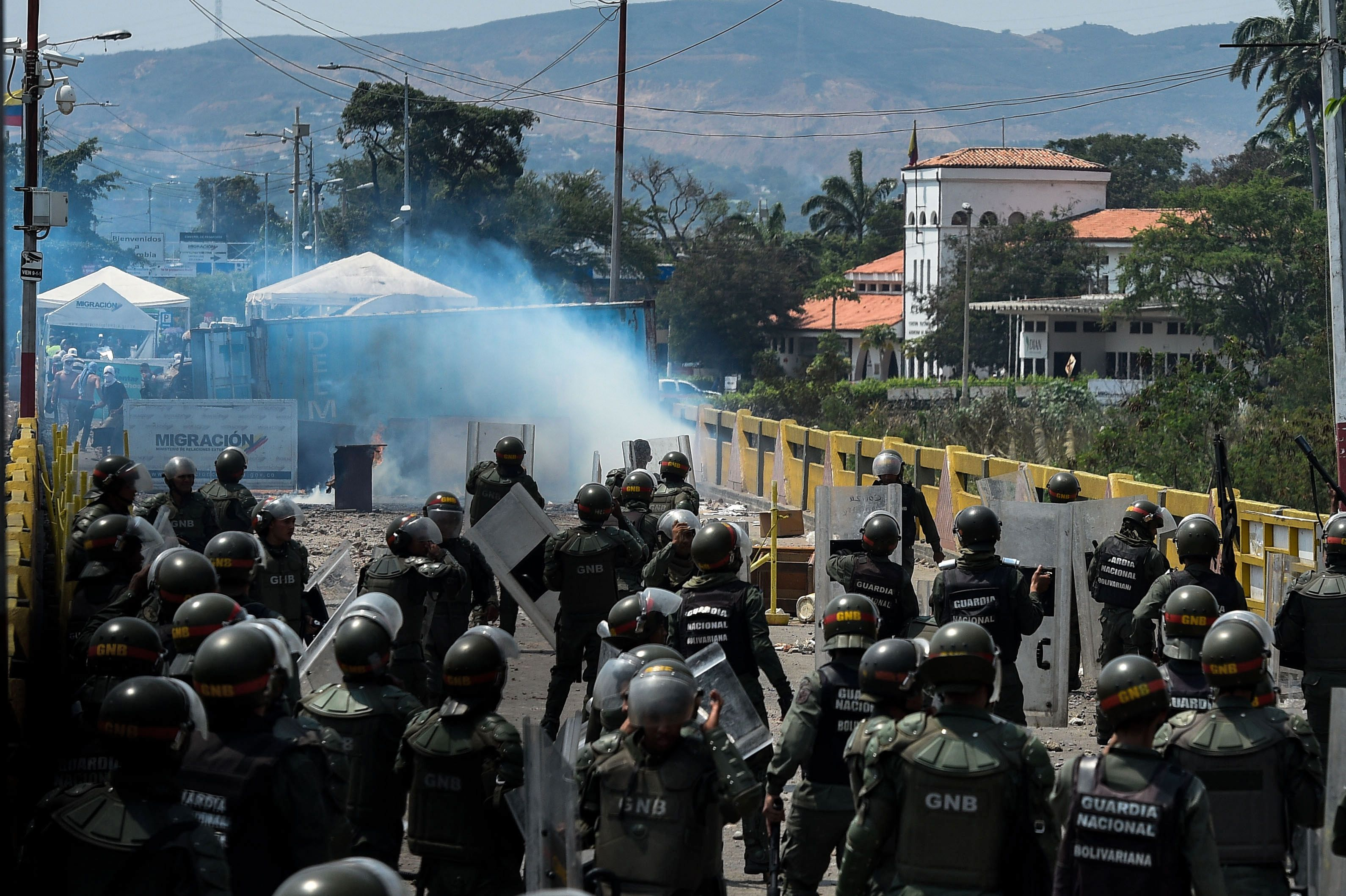 """Members of the Venezuelan National Guard clash with protesters of the Venezuelan opposition on the Simon Bolivar internatioonal bridge in San Antonio del Tachira, Venezuela, on the border with Colombia, on February 24, 2019. - International pressure mounted against Venezuela's leader Nicolas Maduro, with Washington vowing to """"take action"""" after opposition efforts to bring humanitarian aid into the country descended into bloody chaos. Maduro claims the aid is a smokescreen for a US invasion, and has ordered several crossings on Venezuela's borders with Colombia and Brazil closed. (Photo by Federico Parra / AFP)"""