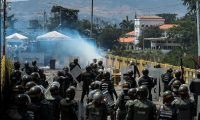 "Members of the Venezuelan National Guard clash with protesters of the Venezuelan opposition on the Simon Bolivar internatioonal bridge in San Antonio del Tachira, Venezuela, on the border with Colombia, on February 24, 2019. - International pressure mounted against Venezuela's leader Nicolas Maduro, with Washington vowing to ""take action"" after opposition efforts to bring humanitarian aid into the country descended into bloody chaos. Maduro claims the aid is a smokescreen for a US invasion, and has ordered several crossings on Venezuela's borders with Colombia and Brazil closed. (Photo by Federico Parra / AFP)"