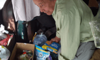 Juan Pablo Figueroa Alfaro, quien vive en un bus abandonado, ordena parte de la ayuda recibida. (Foto Prensa Libre: Cortesía vecinos).