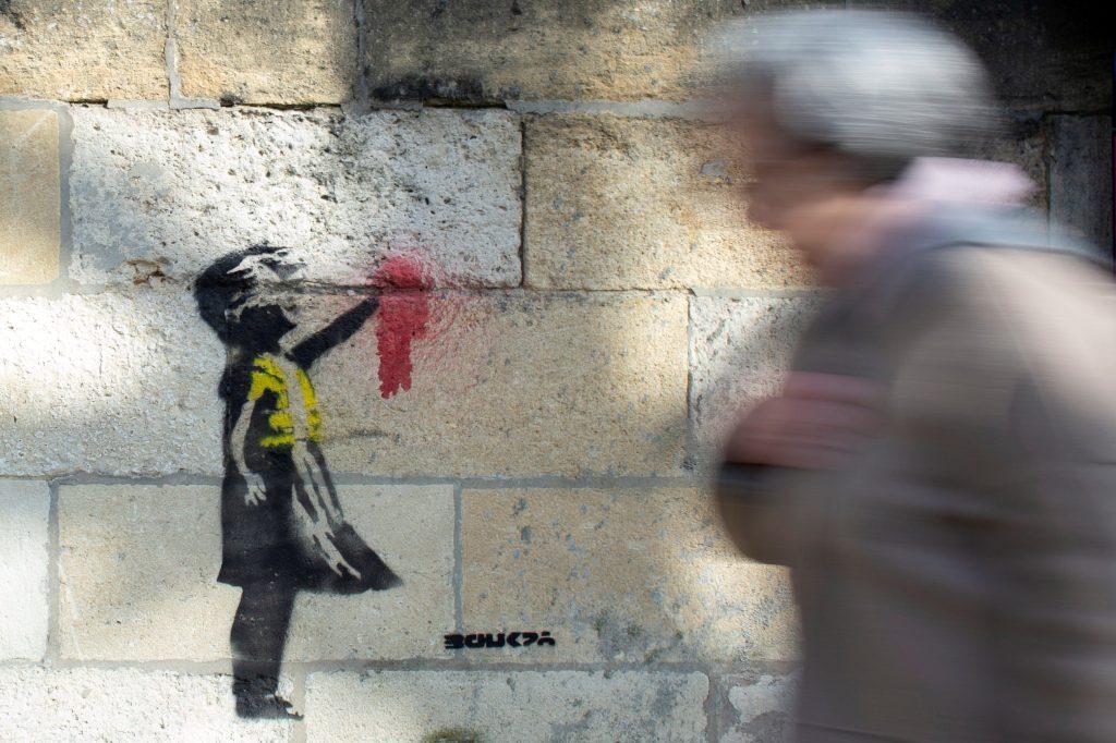 """Una mujer camina  junto a una obra parecida al trabajo de Banksy titulado """"Niña con Globo"""" en la fachada de un edificio en Burdeos, Francia. EFE"""