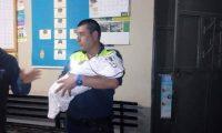 Agente de la PMT carga al bebé abandonado en Chicamán. (Foto Prensa Libre: Héctor Cordero).