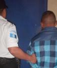 Juan Tista Pérez, quien pretendía agredir a su hijo, es custodiado por una agente de la PNC. (Foto Prensa Libre: PNC).