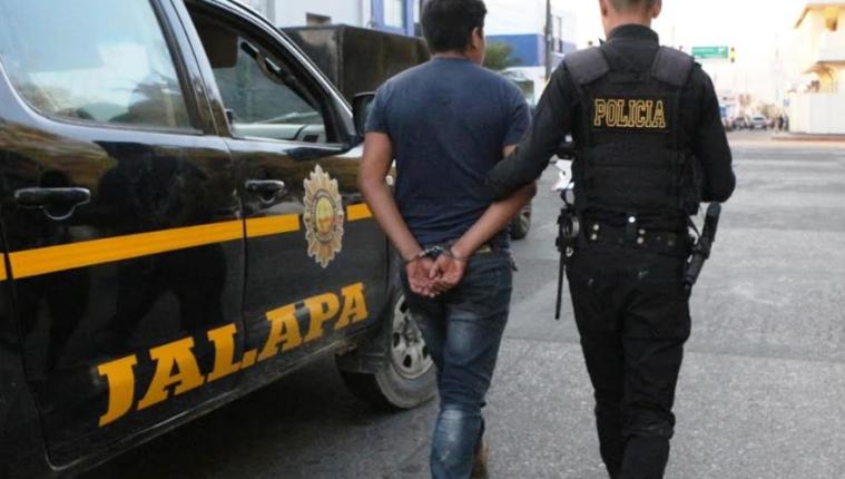 Agente de la PNC custodia a Henry Geovany López Méndez, quien fue capturado en Jalapa por portar licencia de conducir falsa.(Foto Prensa Libre: José Boya).