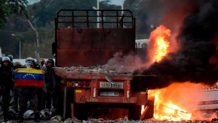 Venezuelan security forces display a national flag next to a truck which was burnt during the weekend when trying to enter the country with humanitarian aid, during clashes with supporters of Venezuelan opposition leader Juan Guaido on the Venezuelan side of the Francisco de Paula Santander International Bridge, as seen from Cucuta, Colombia, on February 25, 2019. - US Vice President Mike Pence and Guaido agreed on a strategy to tighten the noose around President Nicolas Maduro following a meeting with regional allies in Colombia on Monday. (Photo by Raul ARBOLEDA / AFP)