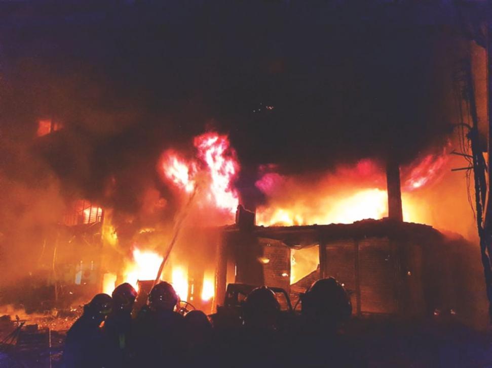 Socorristas tratan de extinguir las llamas en un edificio de Bangladés. (Foto Twitter/@bernamadotcom)
