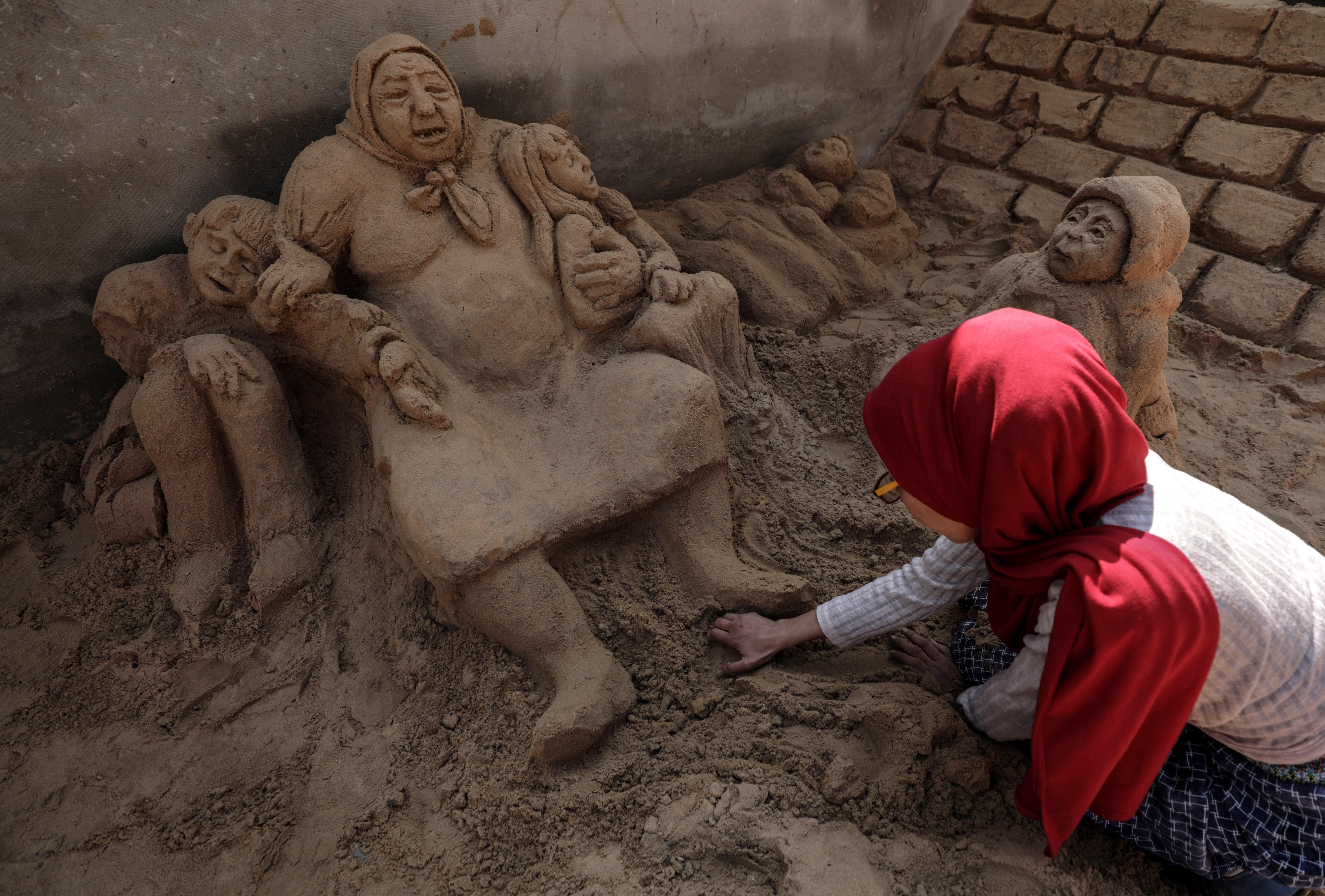 Rana Ramlawi, artista que realiza esculturas de arena relacionadas con el conflicto bélico del país, da los últimos retoques a su última obra en Gaza. EFE