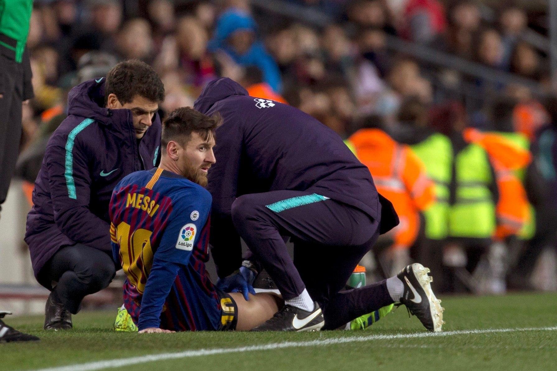 El delantero argentino del FC Barcelona, Leo Messi, atendido por los fisios del equipo blaugrana. (Foto Prensa Libre: EFE)