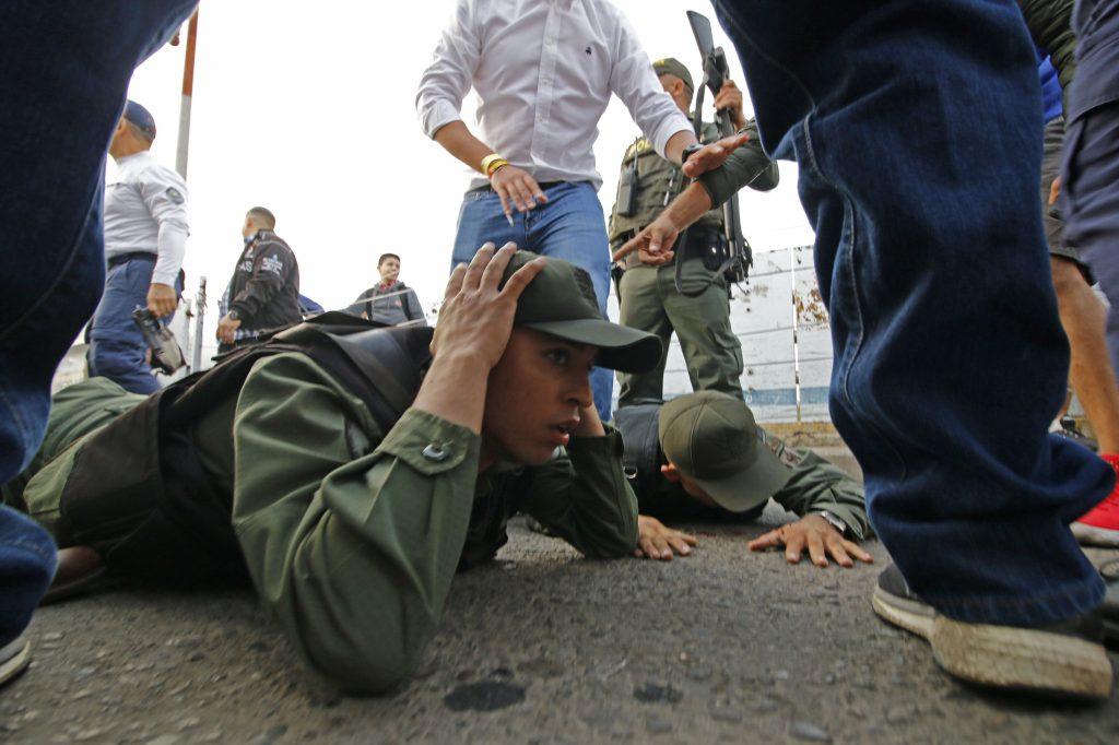 Dos soldados venezolanos yacen en el suelo mientras son detenidos por la policía colombiana después de conducir a Colombia en un vehículo blindado desde el lado venezolano