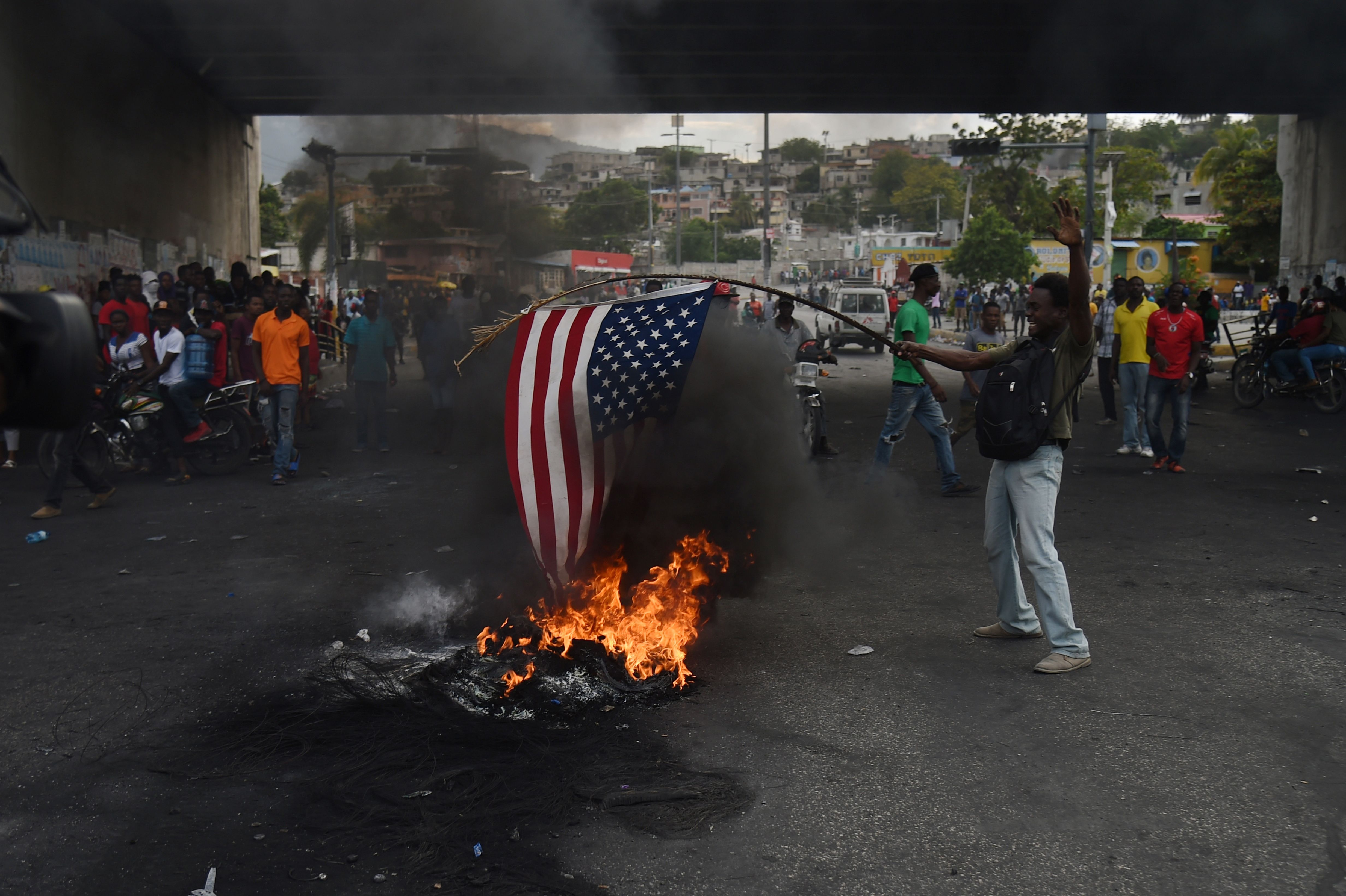 A protester burns a US flag during a demonstration in the Haitian Capital Port-au-Prince, February 15, 2019, on the ninth day of protests against Haitian President Jovenel Moise and the misuse of the Petrocaribe fund. (Photo by HECTOR RETAMAL / AFP)