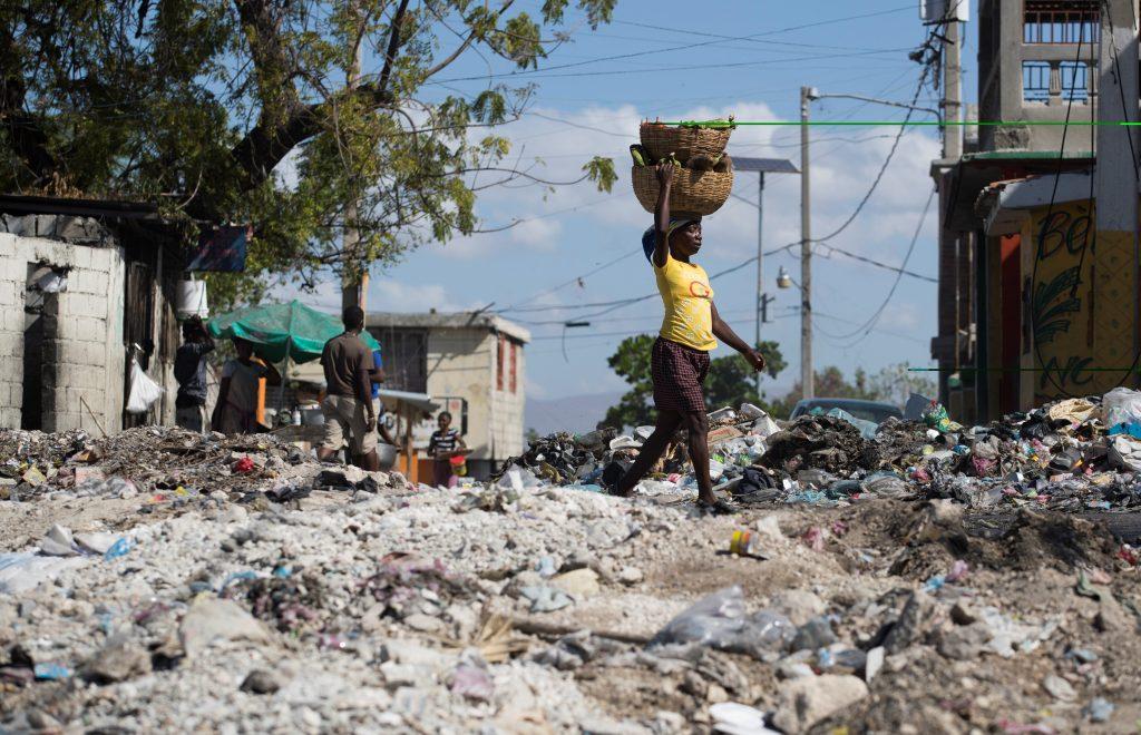 Una mujer camina sobre una calle completamente cubierta por escombros y basura, producto de las violentas protestas de la semana pasada. EFE
