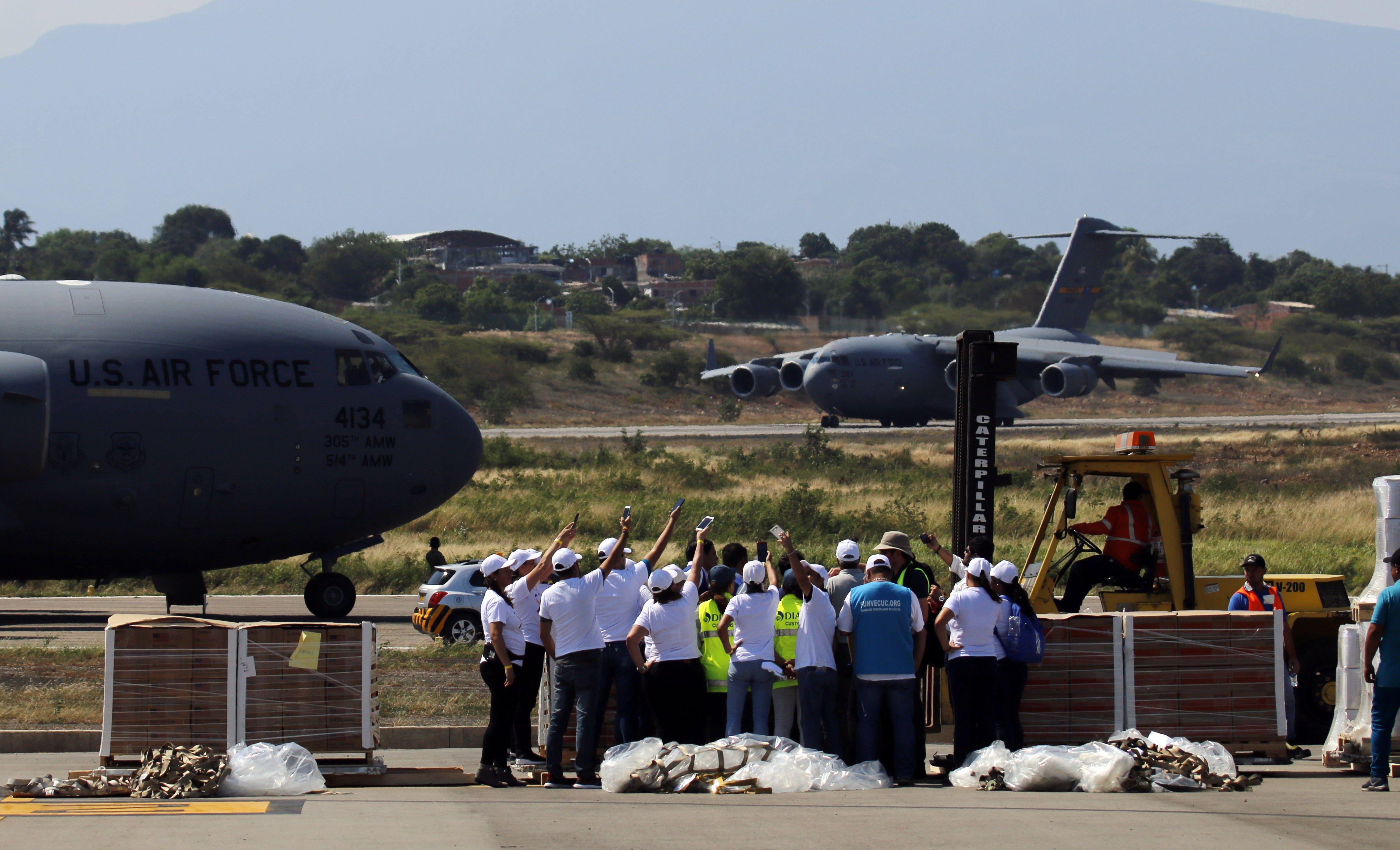 Trabajadores descargan las ayudas del primero de tres aviones de carga C-17 de la Fuerza Aérea de Estados Unidos y celebran el aterrizaje del segundo avión este sábado en el aeropuerto Camilo Daza de Cúcuta (Colombia), con ayuda humanitaria para Venezuela. (Foto, Prensa Libre: Efe).