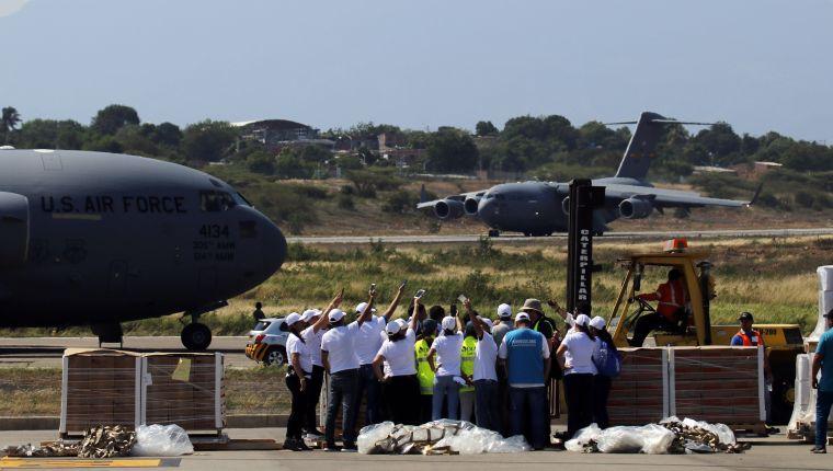CUC116. CÚCUTA (COLOMBIA), 16/02/2019.- Trabajadores descargan las ayudas del primero de tres aviones de carga C-17 de la Fuerza Aérea de Estados Unidos y celebran el aterrizaje del segundo avión este sábado en el aeropuerto Camilo Daza de Cúcuta (Colombia), con ayuda humanitaria para Venezuela procedente de la base aérea de Homestead, en el sur de Miami. EFE/Schneyder Mendoza