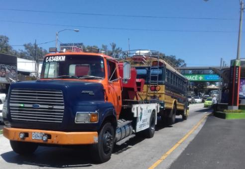 Grúa traslada a predio el bus que fue consignado luego de bloqueos en la calzada Roosevelt. (Foto Prensa Libre: Amílcar Montejo).