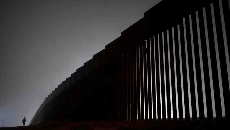 "(FILES) In this file photo taken on December 20, 2018 a man walks next to a reinforced section of the US-Mexico border fence is seen from Tijuana, Baja California state, Mexico. - President Donald Trump promises a shift to sunny optimism in the State of the Union speech but with his congressional Democratic nemesis seated right behind him, will he be able to resist throwing his usual thunderbolts? The White House is flagging an ""optimistic,"" ""unifying,"" even ""visionary"" speech to mark this presidency's midway point. In an excerpt released Friday, Trump predicts Republicans and Democrats can ""break decades of political stalemate."" But the mood in Washington is as hostile as it has been for years following the confrontation between Trump and the Democratic-led House of Representatives over his demand for funding for a US-Mexico border wall. (Photo by Guillermo Arias / AFP)"
