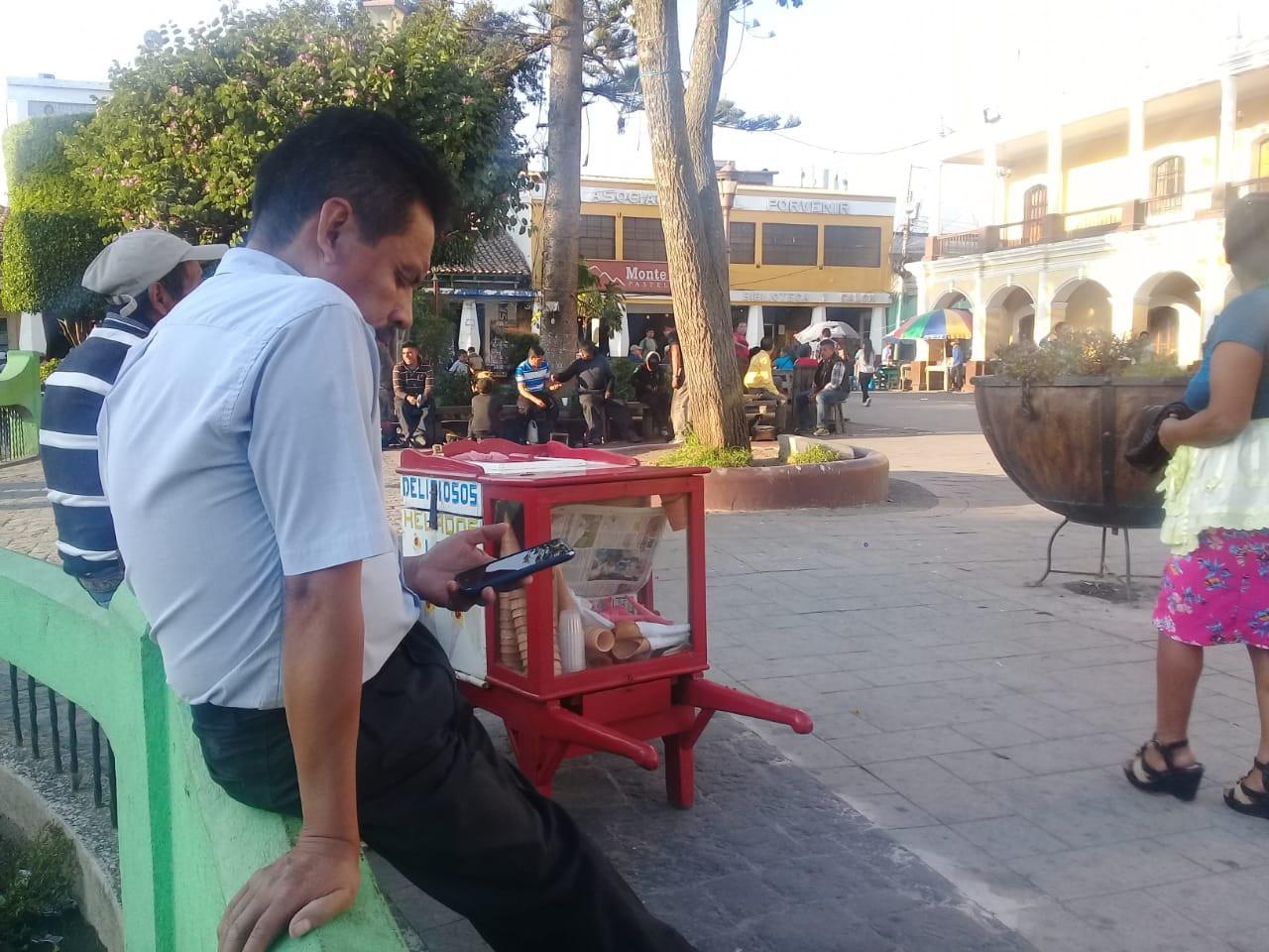 Un usuario de teléfono celular captado en el parque central de Huehuetenango.