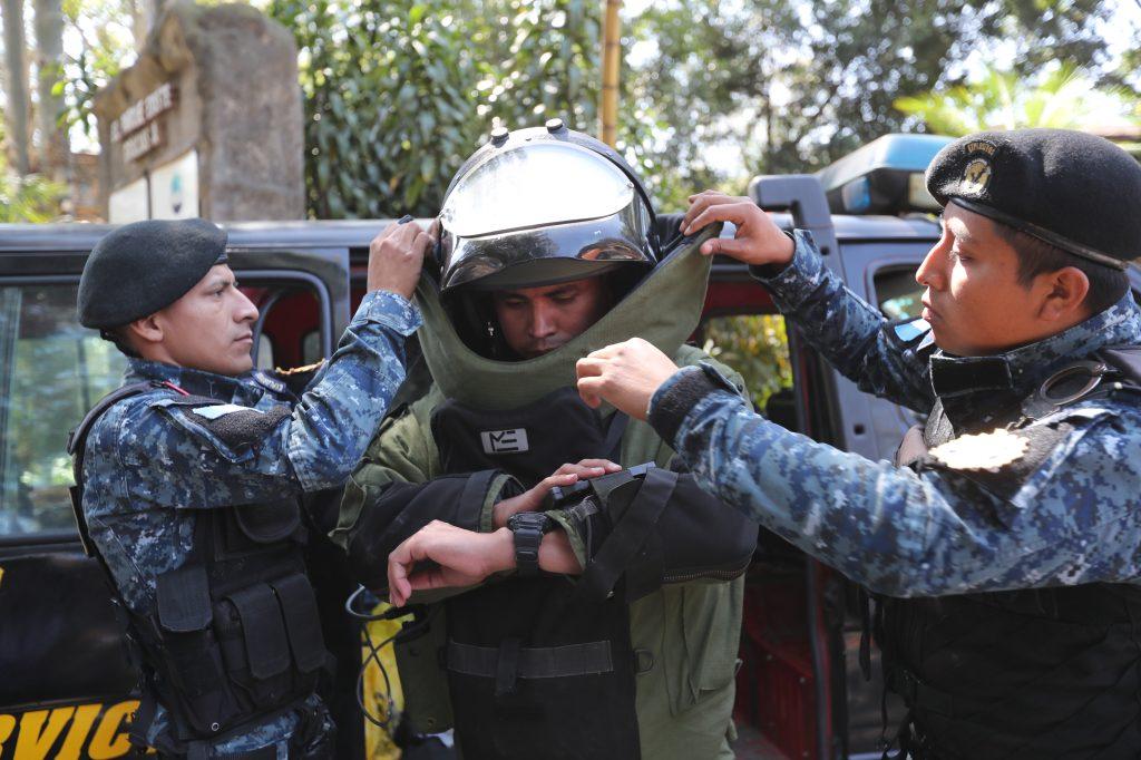 El agente designado para desactivar explosivos, es auxiliado por sus demás compañeros para colocarse el traje protector. Foto Prensa Libre: Erick Avila.