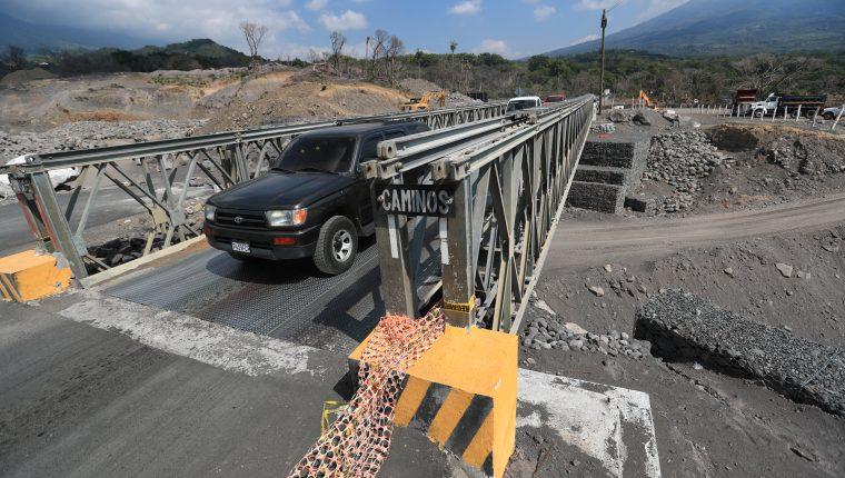Vehículos atraviesan un angosto puente provisional sobre la Ruta Nacional 14, desde donde se puede ver al devastación por la erupción del año pasado. (Foto Prensa Libre: Carlos Hernández Ovalle)