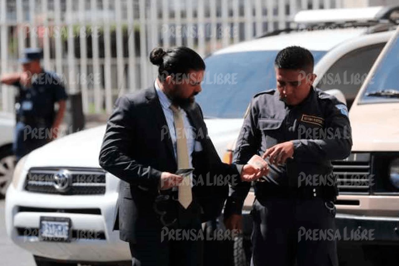Jonathan Harry Chévez entrega un billete de Q50 a un guardia de Presidios. (Foto Prensa Libre)