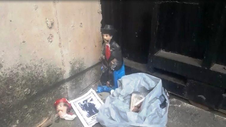 Dos imágenes de San Simón, un libro de oración, dos candelas negras, un alfiler y otros artículos hallados por la PNC. (Foto Prensa Libre: Mario Morales)
