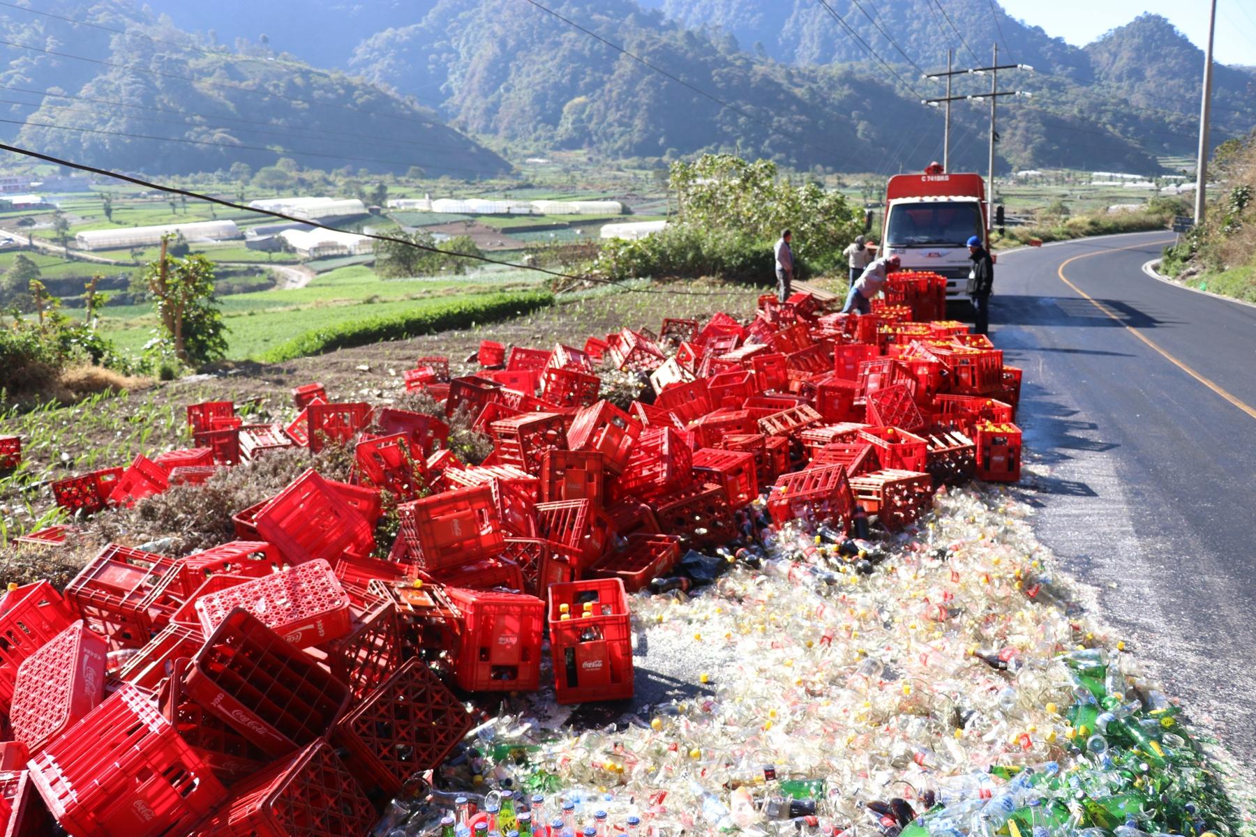 Camión que transportaba aguas gaseosas volcó y el producto quedó tirado en la carretera.  (Foto prensa Libre: María Longo)