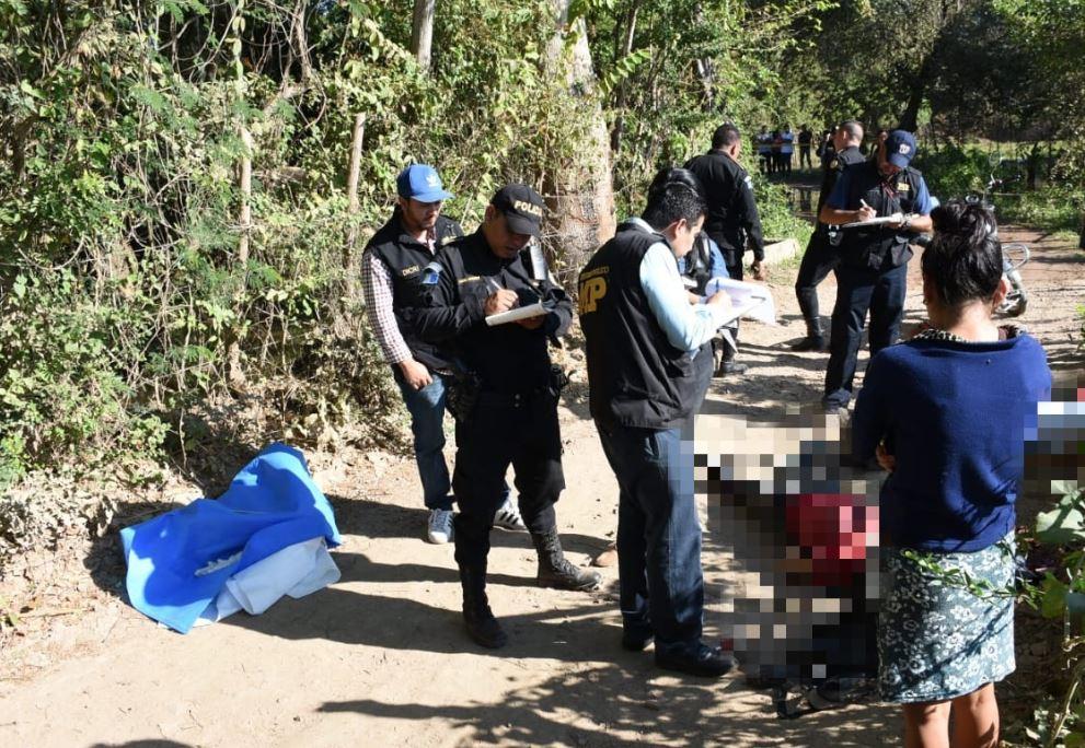 Fiscales y agentes de la PNC trabajan en el lugar donde ultimaron a padre e hijo. (Foto Prensa Libre: Mario Morales)