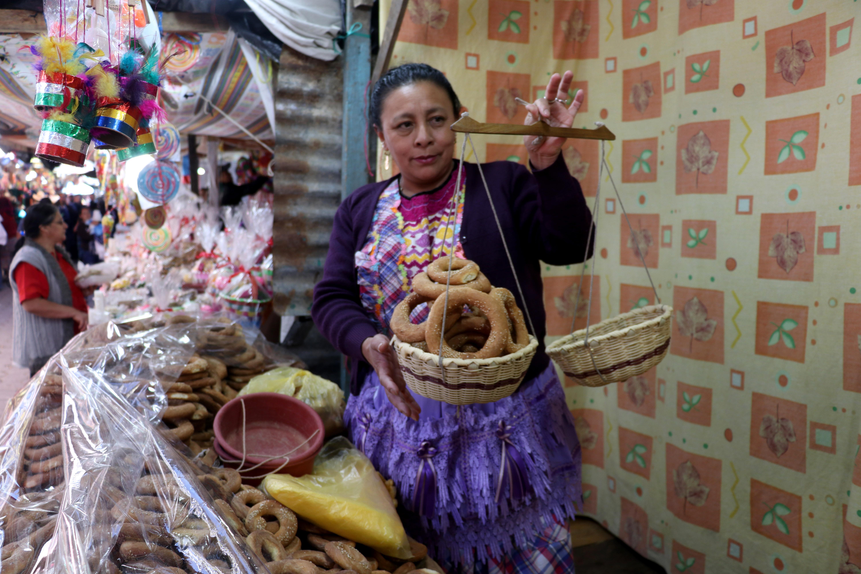 Elizabeth Gómez pesa roscas en una de las ventas de la feria en Chiantla. (Foto Prensa Libre: Mike Castillo)