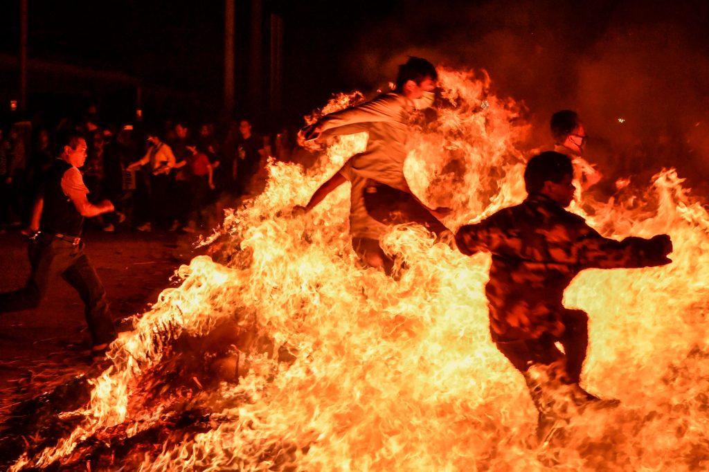 Personas saltan sobre una hoguera durante un evento para celebrar el Festival de los Faroles, que marca el final de las celebraciones del Año Nuevo Lunar, en Haikou, en la provincia de Hainan, sur de China. AFP