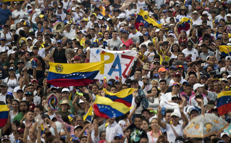 """La gente espera el inicio del concierto """"Venezuela Aid Live"""" con un mensaje de paz. AFP"""