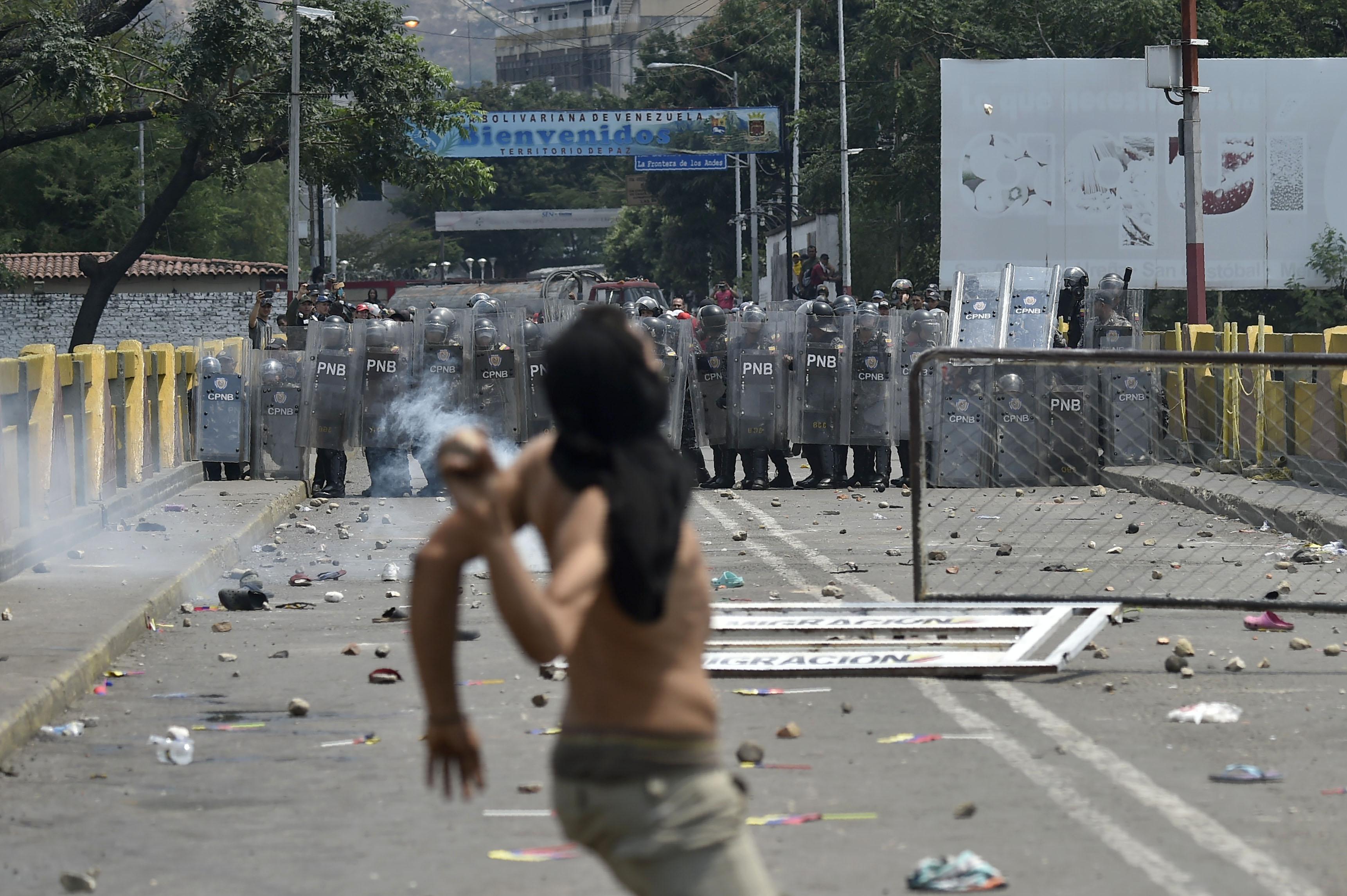 Los manifestantes se enfrentan a la policía nacional venezolana en el puente Simón Bolívar, en Cúcuta, Colombia, luego de que el gobierno del presidente Nicolás Maduro ordenó el cierre temporal de la frontera con Colombia. AFP