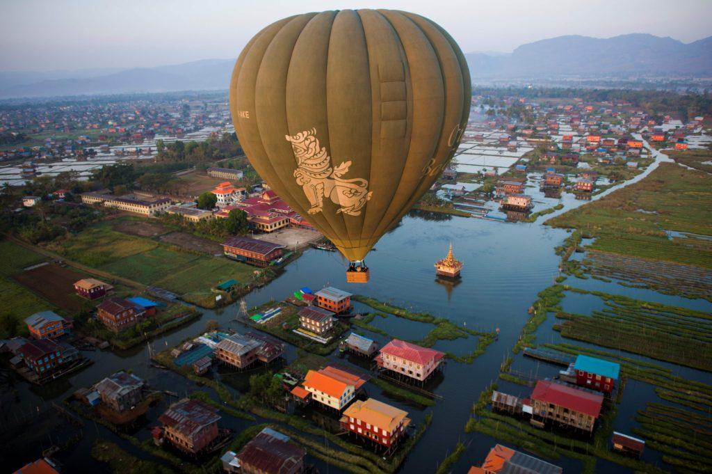 Un globo aerostático vuela sobre casas tradicionales sobre pilotes en el lago Inle en el estado de Shan en Birmania. AFP
