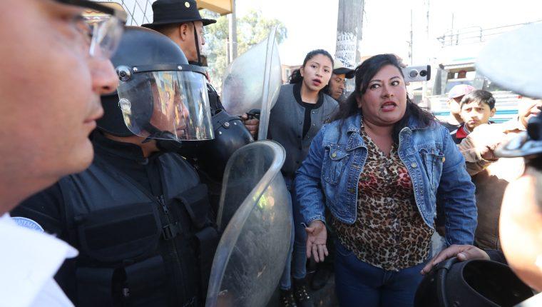 La propietaria de un negocio increpa al gobernador departamental, Julio César Quemé, –izq, con lentes–, por los operativos en la 19 avenida.  (Foto Prensa Libre. Mynor Toc)