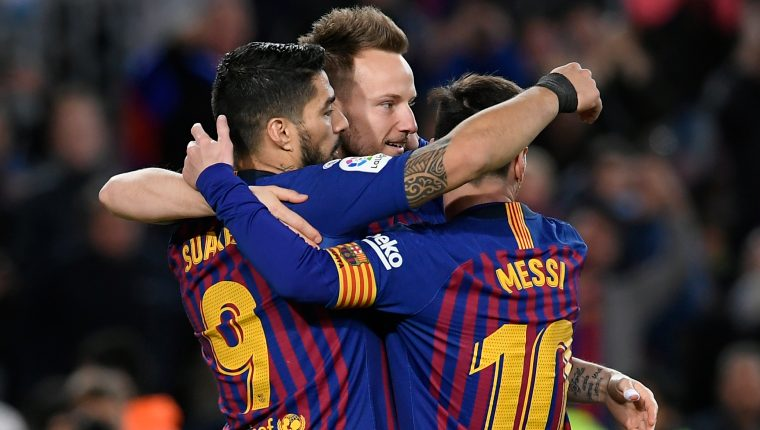 Barcelona's Uruguayan forward Luis Suarez (L) celebrates with Barcelona's Croatian midfielder Ivan Rakitic and Barcelona's Argentinian forward Lionel Messi after scoring during the Spanish league football match between FC Barcelona and Rayo Vallecano de Madrid at the Camp Nou stadium in Barcelona on March 9, 2019. (Photo by LLUIS GENE / AFP)
