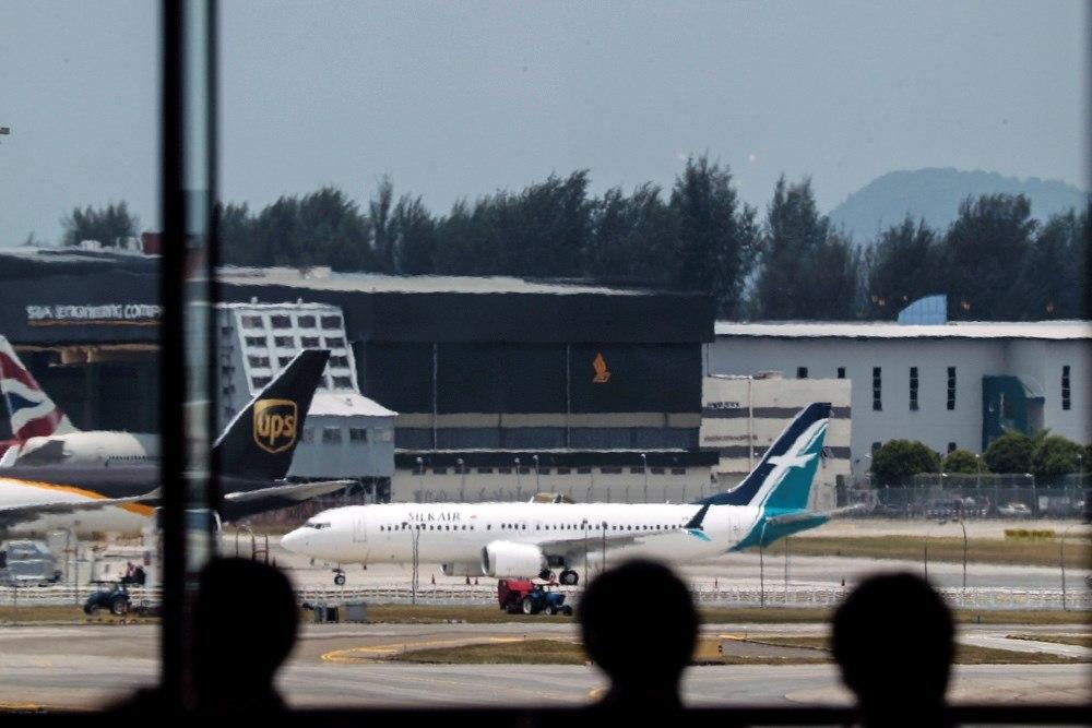 EPA2299. SINGAPUR (SINGAPUR), 12/03/2019.- Varios viajeros observan el avión Boeing 737 Max 8 de la aerolínea Silkair cerca de los hangares este martes en el aeropuerto Changi de Singapur. Las autoridades de Singapur anunciaron la suspensión temporal de todos los vuelos del avión Boeing 737 MAX, a raíz del accidente el domingo de una aeronave de este modelo en Etiopía. EFE/ Wallace Woon