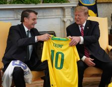 El presidente de Estados Unidos, Donald Trump, recibe una camiseta oficial de la selección de fútbol de Brasil durante la reunión mantenida con su homólogo brasileño, Jair Bolsonaro, en la Casa Blanca.  (Foto Prensa Libre: EFE)