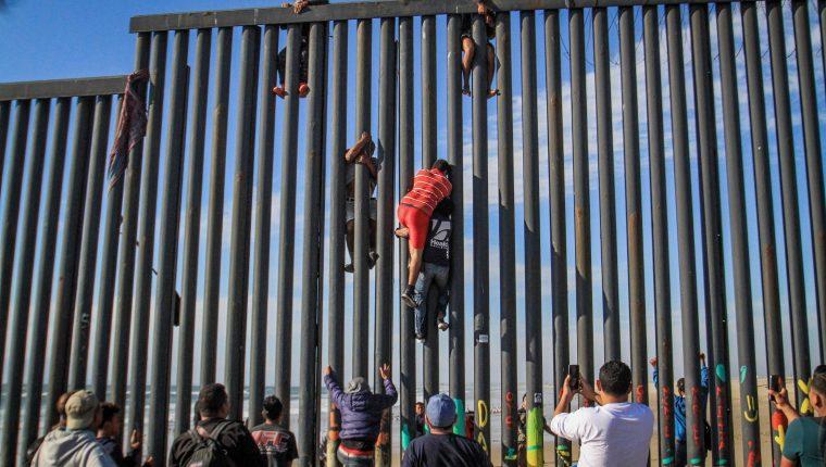 Decenas de migrantes intentan saltar el muro en las playas Tijuana. (Foto Prensa Libre: EFE)