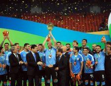 El defensa y capitán de la selección uruguaya, Diego Godín, levanta el trofeo tras la final de la China Cup. (Foto Prensa Libre: EFE)