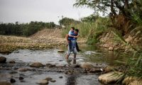 "A man carrying a student cross the Tachira river through ""Trochas"" --illegal trails--, near the Simon Bolivar international bridge, from San Antonio, Venezuela, to Cucuta, Colombia on March 4 , 2019. - Venezuela's opposition leader Juan Guaido was mobbed by supporters, media and the ambassadors of allied countries as he returned to Caracas on Monday, defying the threat of arrest from embattled President Nicolas Maduro's regime. (Photo by Juan Pablo Bayona / AFP)"