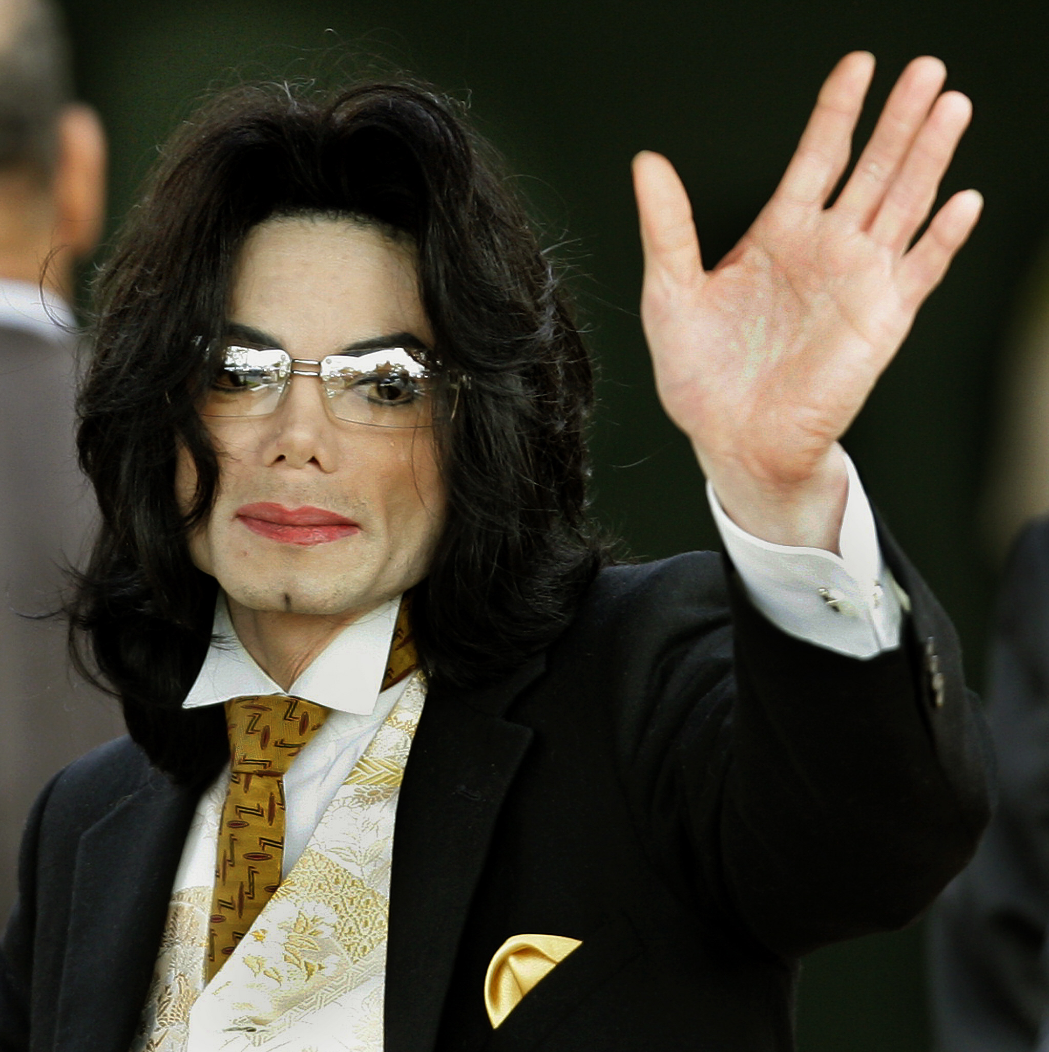 """(FILES) In this file photo taken on June 03, 2005, Michael Jackson waves as he arrives at the Santa Barbara County courthouse in Santa Maria, California. - The creators of """"The Simpsons"""" have shelved one of the animated series' classic episodes because it features Michael Jackson's voice, the show's executive producer told The Wall Street Journal on March 8, 2019. Simpsons producers made the unanimous decision after viewing the bombshell documentary """"Leaving Neverland,"""" which revives pedophilia accusations against the late megastar in excruciating detail. (Photo by Timothy A. CLARY / AFP)"""