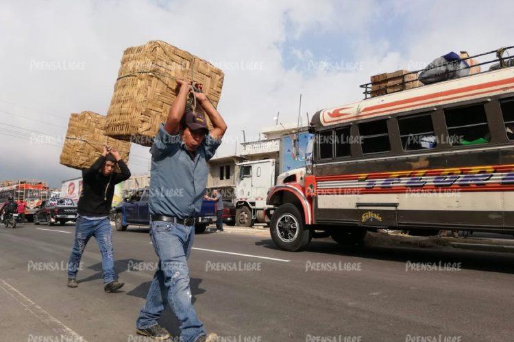 Algunas personas cargan bultos ante la paralización del tránsito vehicular.