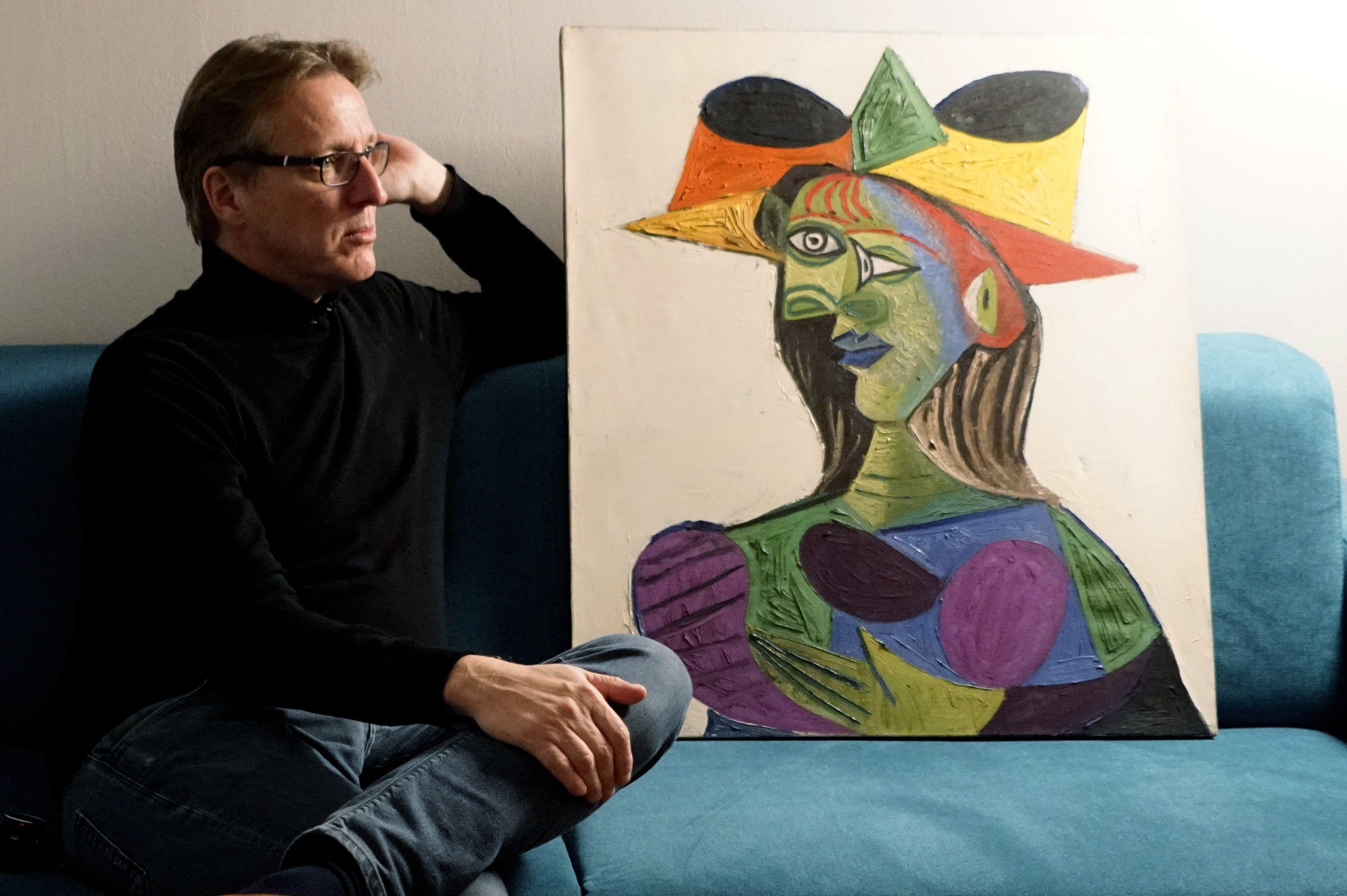 """Arthur Brand sentado junto a la pintura """"Busto de mujer"""", un cuadro que fue hallado 20 años más tarde de haber sido robado. (Foto Prensa Libre: EFE)"""