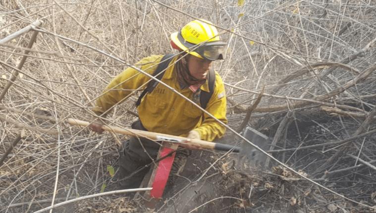 Bombero efectúa tareas de mitigación en uno de los incendios forestales registrados en las últimas horas. (Foto Prensa Libre: Conred).