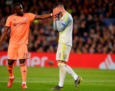Lyon's French forward Tanguy NDombele Alvaro (L) conforts Lyon's Portuguese goalkeeper Anthony Lopes during the UEFA Champions League round of 16, second leg football match between FC Barcelona and Olympique Lyonnais at the Camp Nou stadium in Barcelona on March 13, 2019. (Photo by Josep LAGO / AFP)