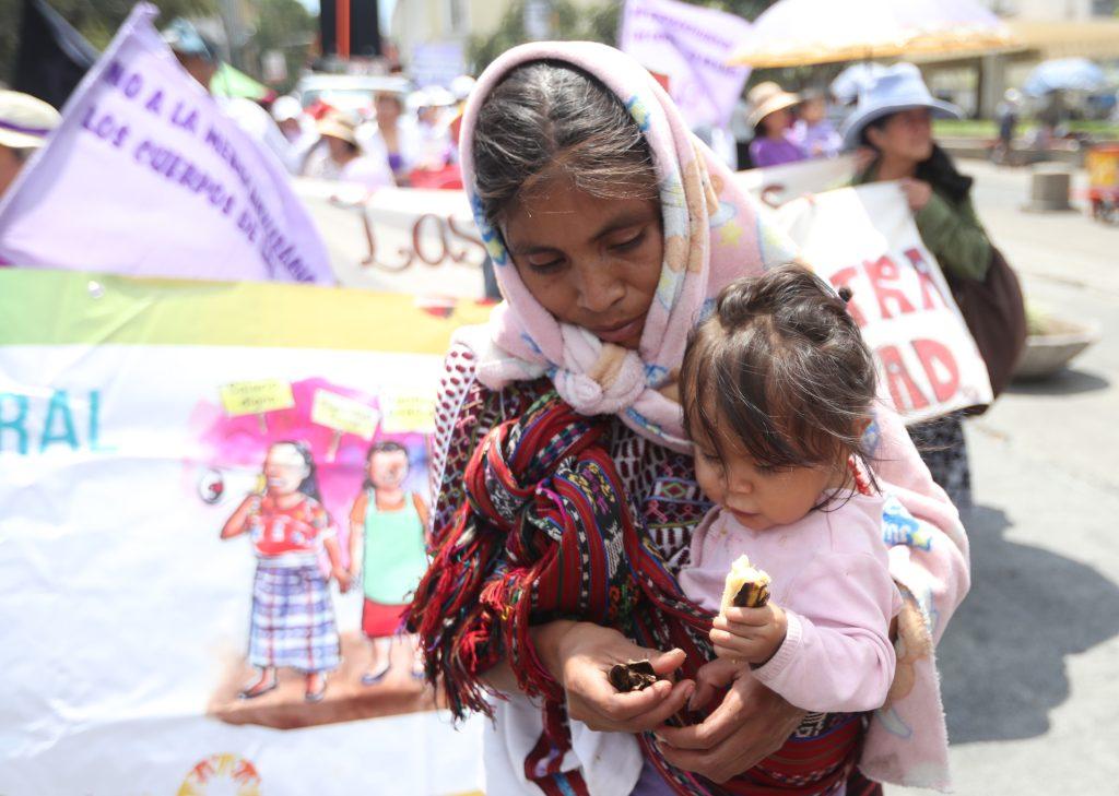 Doña María comparte un banano con Marcela, su hija de un año, mientras participan en la marcha. (Foto Prensa Libre: Óscar Rivas)