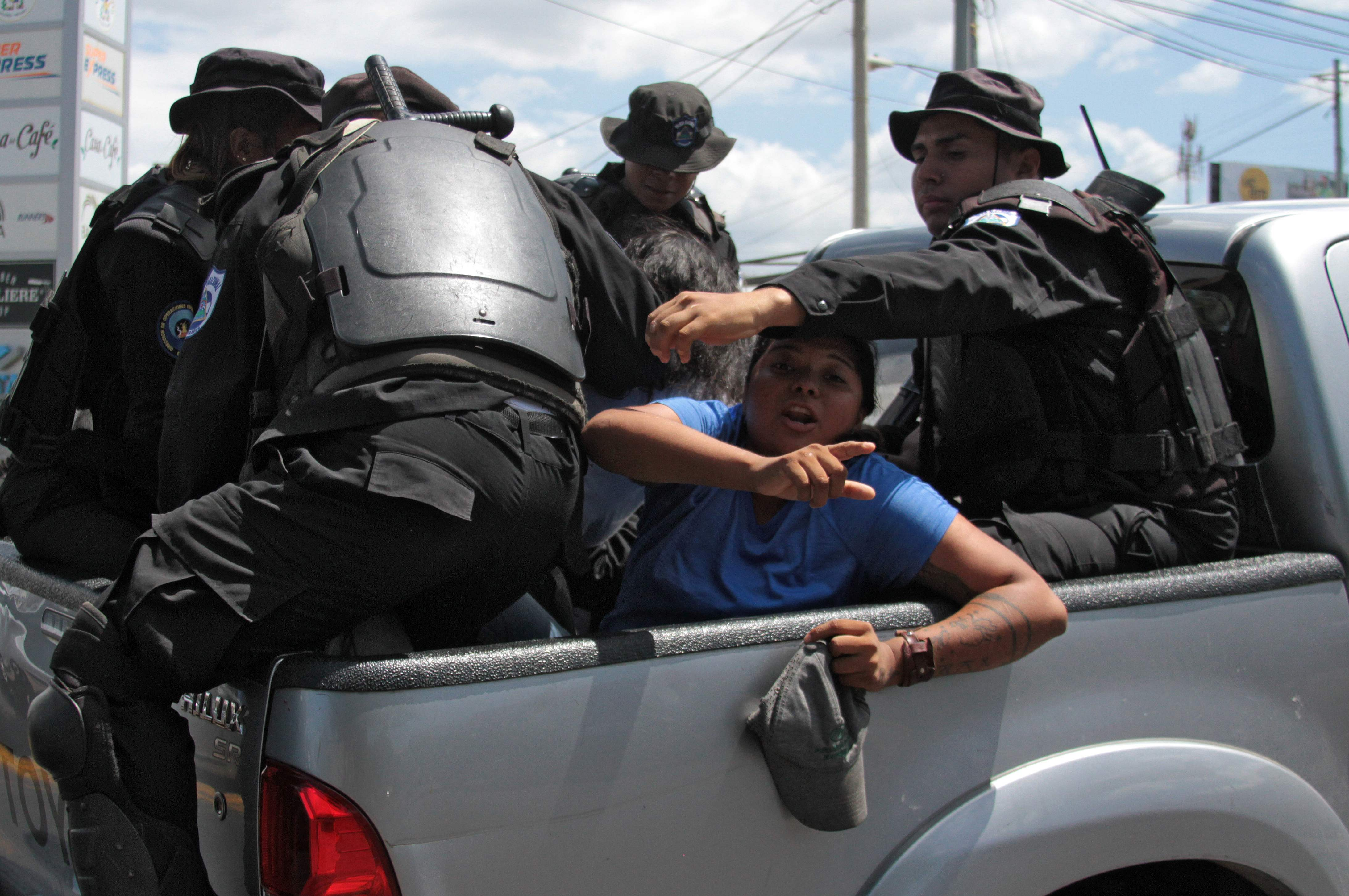 Nicaraguan riot police officers leave with two people arrested while their were heading to a demonstration called by opposition groups to demand the government the release of those arrested for taking part in anti-government protests, in Managua on March 16, 2019. - Nicaragua on Friday released 50 prisoners held for participating in anti-government protests, giving a fresh impetus to peace talks on ending the country's long running political crisis. More than 700 people were detained during a deadly crackdown on rallies that began last April and quickly grew into broad opposition to President Daniel Ortega iron-fisted rule. (Photo by Maynor Valenzuela / AFP)