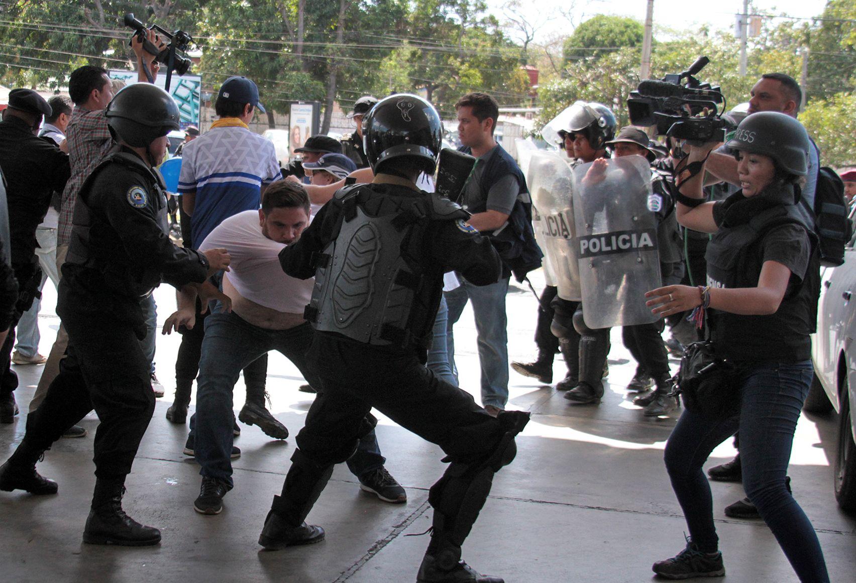 Oficiales de la policía antidisturbios de Nicaragua luchan con el camarógrafo de la AFP Luis Sequeira (L) y sus colegas ante una protesta convocada por grupos de la oposición para exigir al gobierno la liberación de los arrestados por participar en protestas. (Foto Prensa Libre: AFP)
