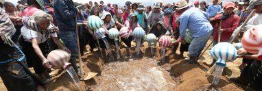 Mujeres de Nahualá echan agua a la tumba de la familia Perechú Cotiy. (Foto Prensa Libre: Mynor Toc)