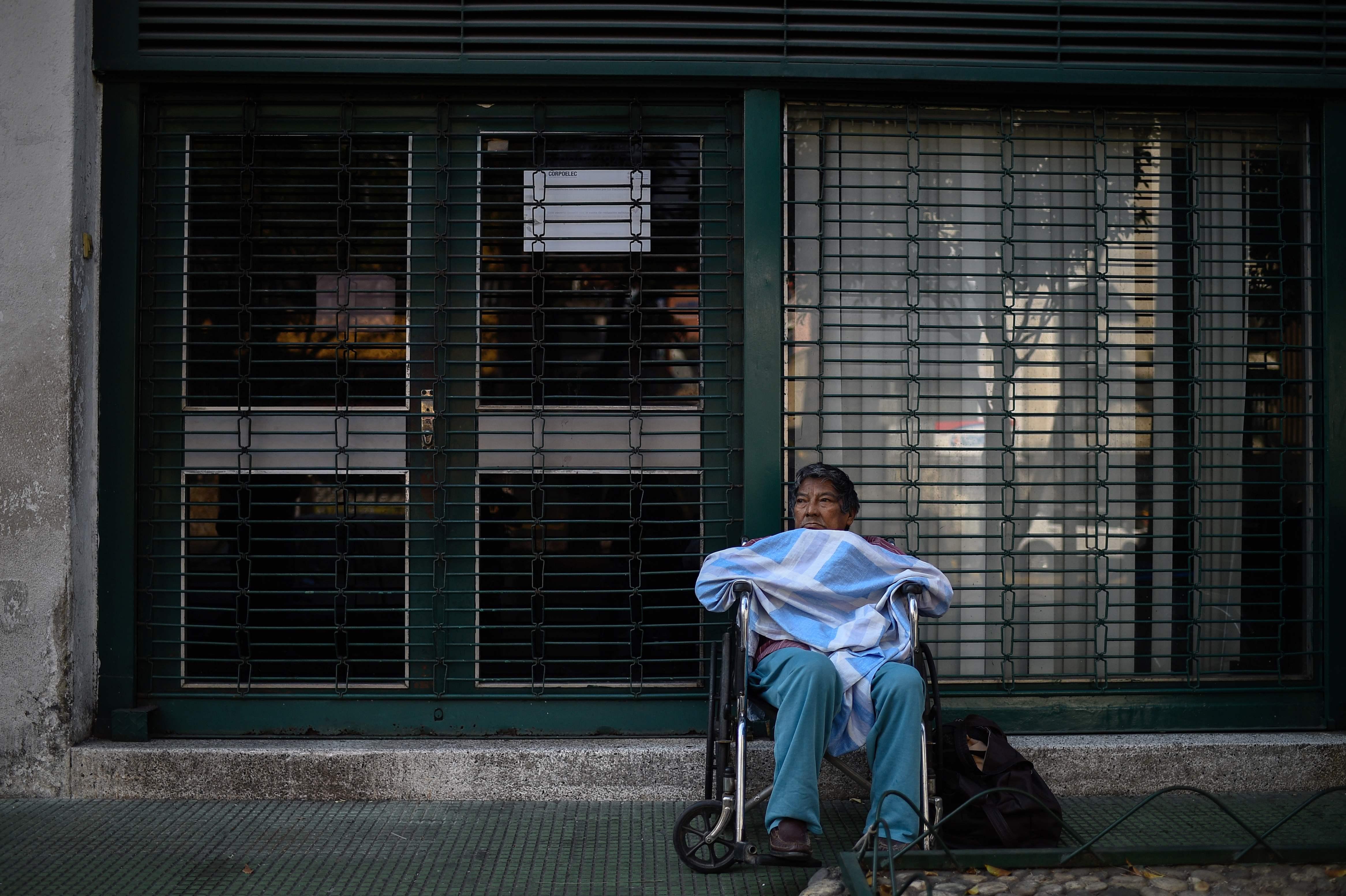 Un paciente en tratamiento de diálisis espera fuera de una clínica cerrada durante un apagón en Caracas. (Foto Prensa Libre: AFP)